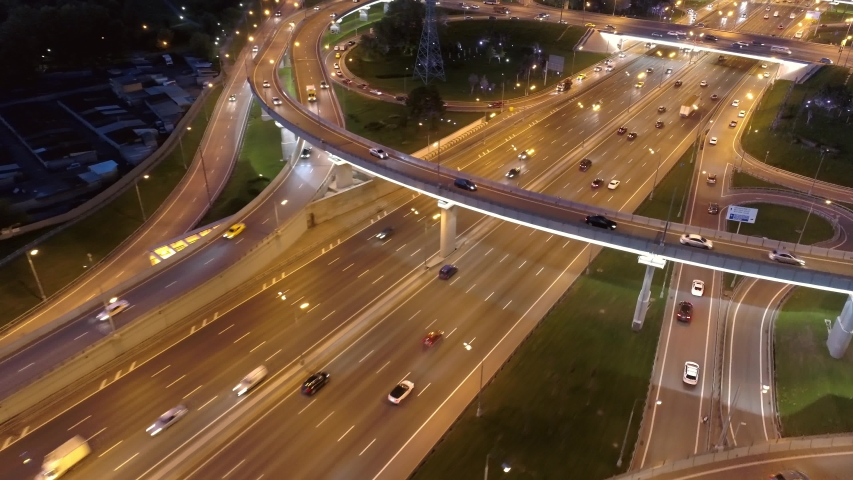 Flight low over night road junction multi-level overpass multi-lane active traffic. Follow cars with headlights on go along an illuminated highway. Transportatian large city Cinematic aerial 4K | Shutterstock HD Video #1037489264