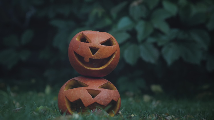 Spooky pumpkins on the grass. One of the pumpkins falls on other two spooky lanterns pumpkins in slow motion. | Shutterstock HD Video #1037749454
