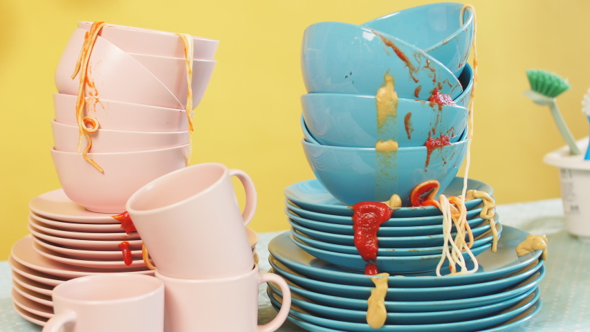 Kitchen table is full of dirty dishes, isolated yellow background. Studio shot. | Shutterstock HD Video #1037972894
