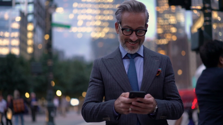 Slow motion of smiling mature lawyer in expensive suit messaging with customers via cellular device while walking in financial district,successful businessman in optical eyewear searching trading news | Shutterstock HD Video #1037982434