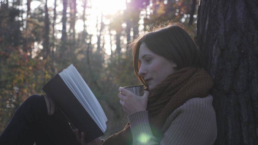 Glamorous brunette woman traveler drinking hot beverages from thermos cup, reading book and nostalgic in fall forest park at sunset | Shutterstock HD Video #1038053354