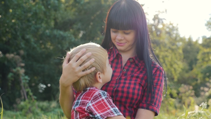 A happy family. Mom with son close-up on the nature. The boy snuggles up to his mother playing games with his mother. Family values. Love for the family. Family relationship concept | Shutterstock HD Video #1038253874