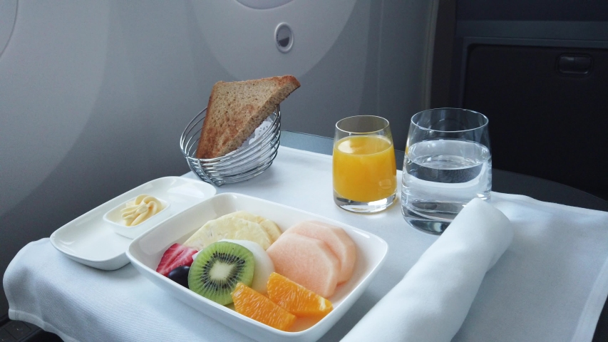 Delicious breakfast with fruit served on board of business class airplane. Tray of food in the airplane. Tray of food on the plane, business class travel.   | Shutterstock HD Video #1038447224