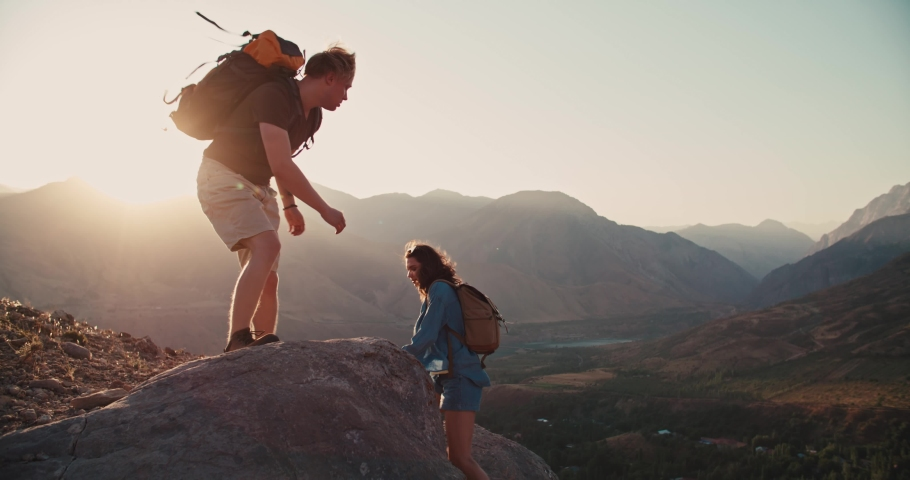Young caucasian couple backpacking together, helping each other on way up, exploring beautiful mountains - adventure, freedom concept 4k footage | Shutterstock HD Video #1038467354