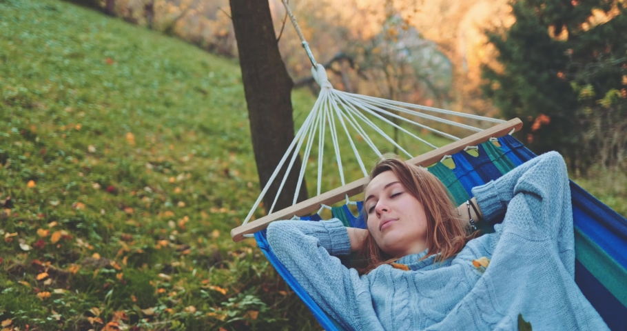 Woman Relaxes in a Hammock in Autumn. SLOW MOTION. Young woman daydreams, unwinds in a calm fall outdoor, rural country nature with colourful forest in background. Cozy morning or evening. | Shutterstock HD Video #1038490394