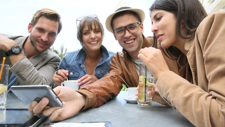 Young people at coffee shop table looking at pictures on smartphone | Shutterstock HD Video #10385984
