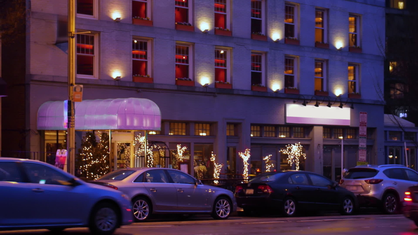 A nighttime outside exterior (NX) side establishing shot of a typical city corner bar or restaurant on a late winter day.   | Shutterstock HD Video #1038807944