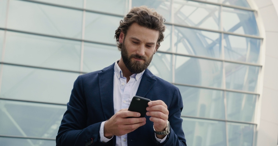 Handsome Businessman browsing his Smartphone near modern Office Building. Attractive Man is smiling and wearing Smart-casual Style. Social Networking. Luxury Lifestyle. Smartphones. Apps. | Shutterstock HD Video #1038809864