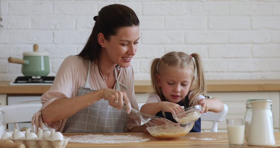 Cute little kid daughter helping mom adding flour to eggs preparing dough for cookies together in modern kitchen, happy mother teaching small child girl learning cooking baking cake pastry at home | Shutterstock HD Video #1038952454