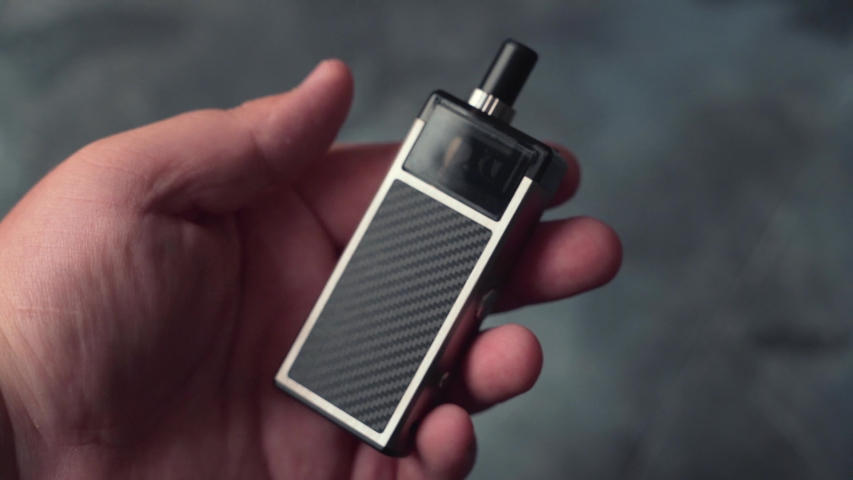 Vape pod in male hand or pod mod close up - newest generation of vaping products | Shutterstock HD Video #1038995294