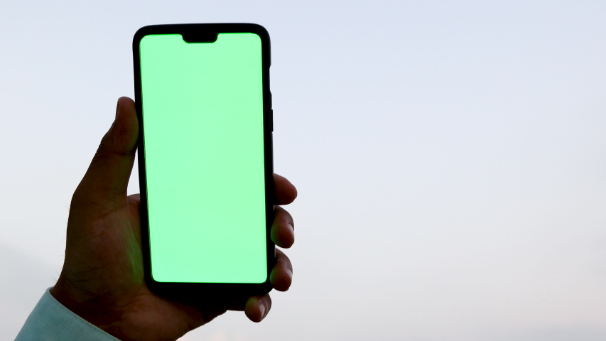 Man holding a smartphone with green screen against the sky | Shutterstock HD Video #1039008374