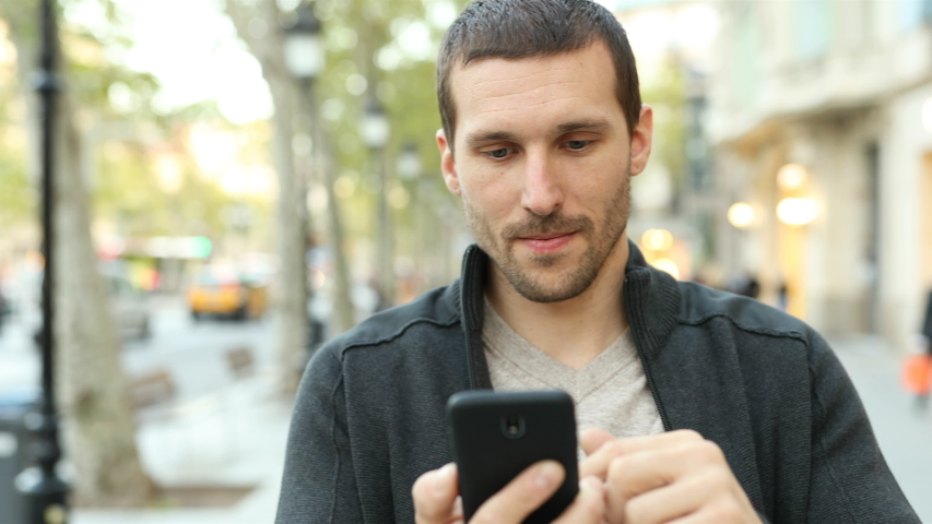 Front view of a happy adult man using smart phone walking towards camera in the street | Shutterstock HD Video #1039011704