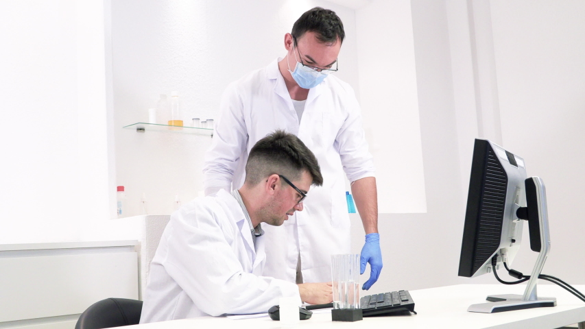 Colleagues discuss lab work on new drugs and viruses   Shutterstock HD Video #1039130774