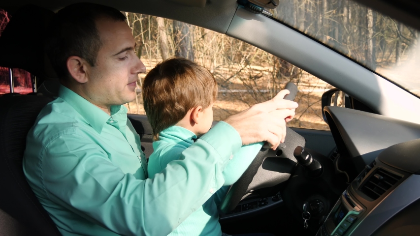 Happy child turns the wheel in the car. Father shows the device of the car. The concept of family, education and car travel.   Shutterstock HD Video #1039196024