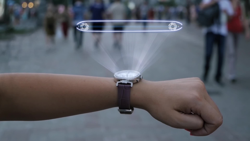 Female hand with futuristic smartwatch shows HUD hologram with text IPO. Woman uses holographic technology of future on wristwatch against background of evening city with people | Shutterstock HD Video #1039205234