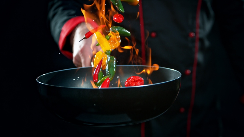 Super Slow Motion Shot of Chef Holding Frying Pan and Falling Chilli Peppers into Fire at 1000fps. | Shutterstock HD Video #1039227434
