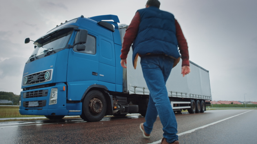 Truck Driver Crosses the Road in the Rural Area and Gets into His Blue Long Haul Semi-Truck with Cargo Trailer Attached. Logistics Company Moving Goods Across Countrie and Continent | Shutterstock HD Video #1039239764