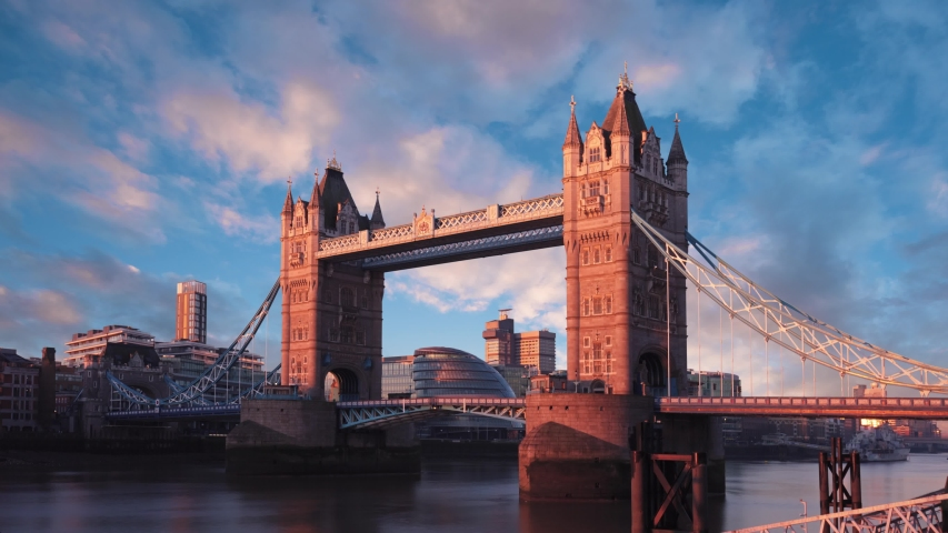 A beautiful scene showing the famous London, England landmark of Tower Bridge during a winter morning sunrise. Colorful time lapse with dramatic, interesting clouds.   Shutterstock HD Video #1039329494