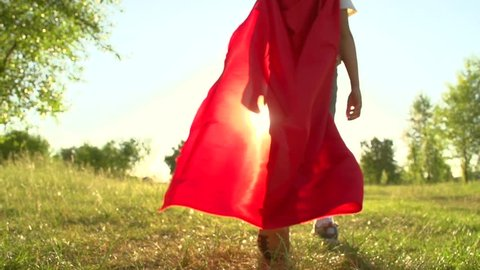 Superhero kid outdoors. Little Boy wearing Super hero costume. Curious Superhero Boy walking away from camera over sunset background. Slow motion 240 fps, high speed camera. Full HD 1080p