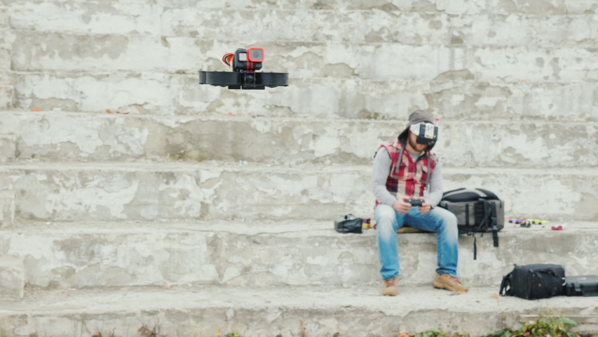 A man in a helmet with telemetry controls a drone that flies in front of him | Shutterstock HD Video #1039609994