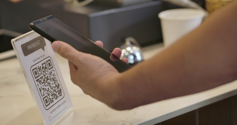 Customer using smartphone for scanning QR code for paying at coffee shop. 4K QR code cashless payment concept. | Shutterstock HD Video #1039730924