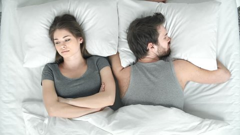 Above view of troubled woman lying in bed by the side of her sleeping husband