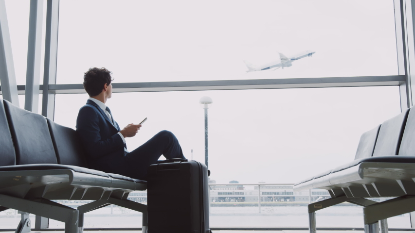Businessman Sits In Airport Departure Lounge Using Mobile Phone With Plane Taking Off In Background | Shutterstock HD Video #1039964774