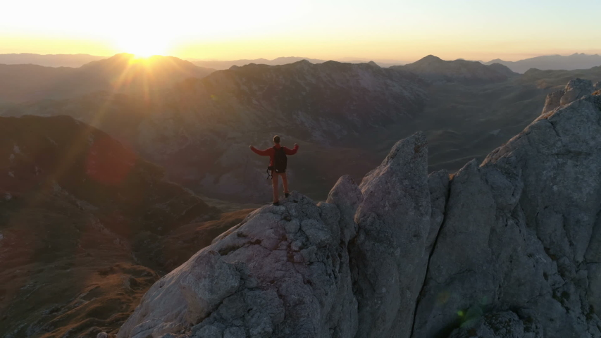 Aerial epic shot of a man hiking on the edge of the mountain in beautiful sunset, slow motion #1040029154