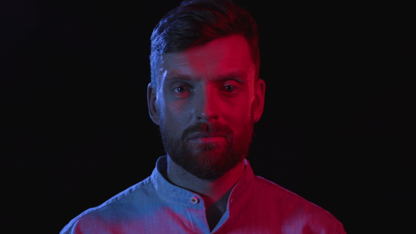 Portrait of Serious Man on Black Background. Face Expression in Colour Filter of Trendy Neon Uv Light. Young Businessman Looking at Camera Closeup Indoors. Sight of Nice 30s Model in Center of Studio   Shutterstock HD Video #1040040914