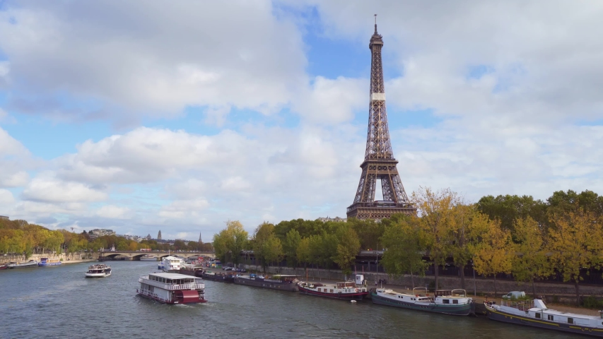 Amazing view of the Eiffel tower from Bir-Hakeim bridge, over the river Seine , Paris, France. Paddle steamer on river at a cloudy but sunny autumn day | Shutterstock HD Video #1040064284