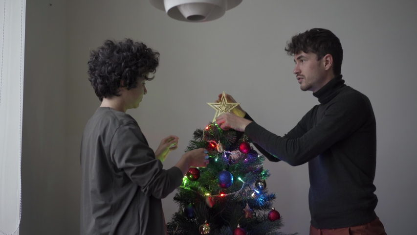Young couple decorates Christmas tree with toys on the eve of the holiday.   Shutterstock HD Video #1040185634