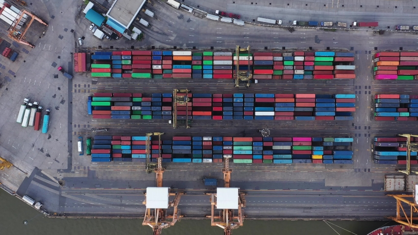 Aerial top view over international cargo ship at industrial import-export port prepare to load containers with big container loader ship vessel. Oversea international Business. | Shutterstock HD Video #1040250764