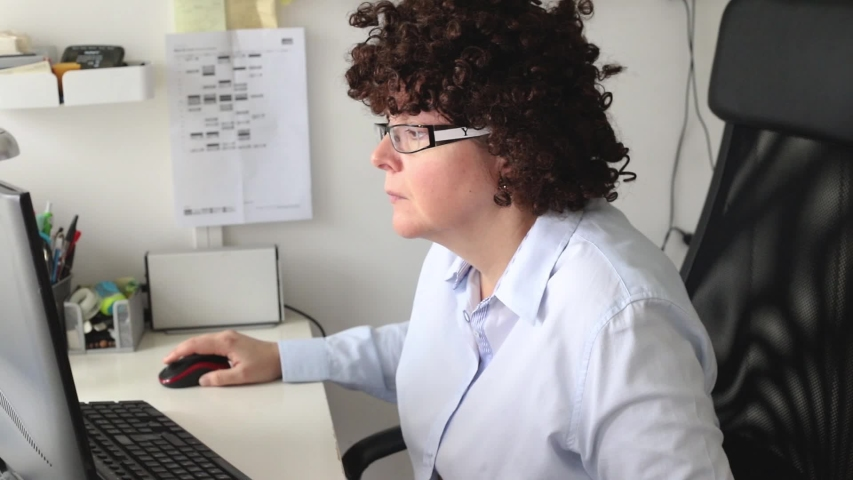 Woman working in the office and biting her nails | Shutterstock HD Video #1040325554
