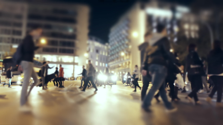 Anonymous Crowd Of Pedestrians Cross A Busy City Intersection At Night.Gimbal shot of a diverse mixed  big silhouetted crowd of people walking and crossing a busy city street.No logos/faces visible. #1040342564