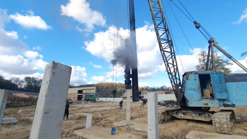 Machine drives into the ground piles construction. Construction of the Foundation of reinforced concrete structures. | Shutterstock HD Video #1040440694
