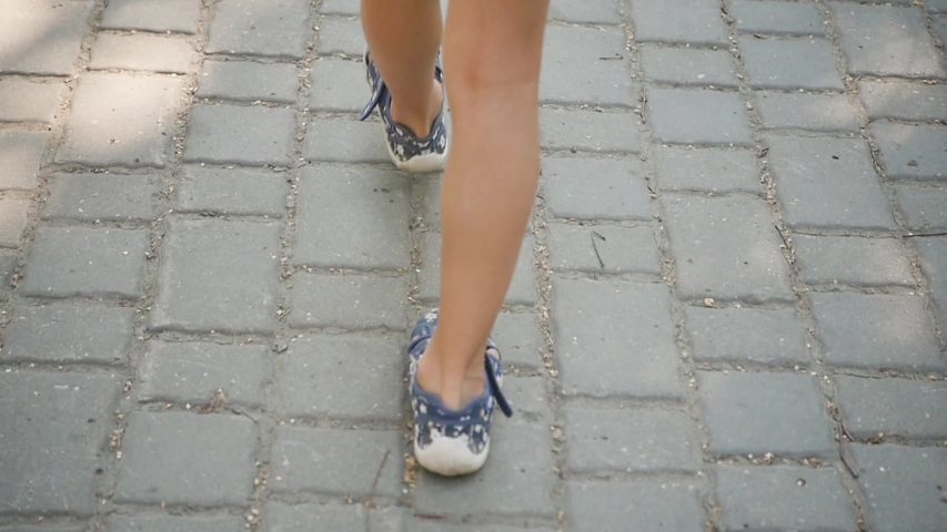 A little girl in shorts is walking in the summer city. The legs of a little girl. Close-up. Slow motion | Shutterstock HD Video #1040519564