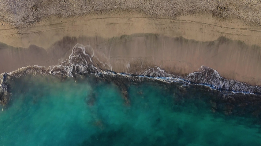 Top view of the desert beach on the Atlantic Ocean. Coast of the island of Tenerife. Aerial drone footage of sea waves reaching shore