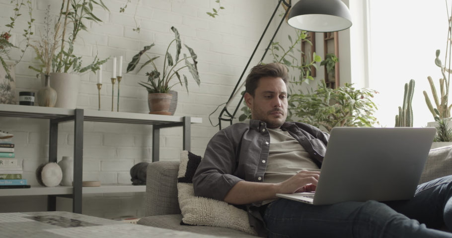 Adult man working from home on laptop on sofa | Shutterstock HD Video #1040631224