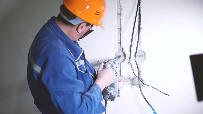 Electrician in hard hat and uniform  works with hammer drill | Shutterstock HD Video #1040649704