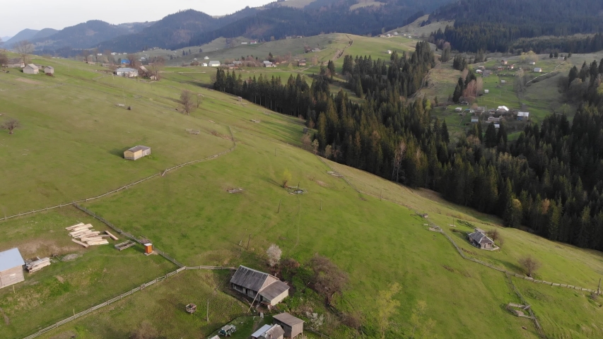 Beautiful aerial drone footage of little highland village surrounded with Carpathian mountains and green forest.Travel destination for active tourism in Western Ukraine. | Shutterstock HD Video #1040687324