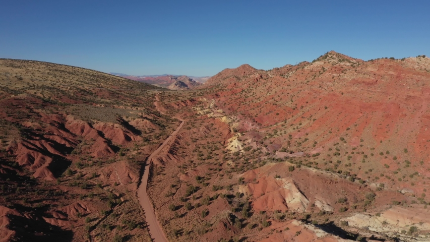 Dirt road in desert with red sand at sunset light. Mountain range of red rocks brick canyon formation. High cliffs of colorful sandstone in dry desert of Western Usa. Aerial view, drone flies forward | Shutterstock HD Video #1040726234