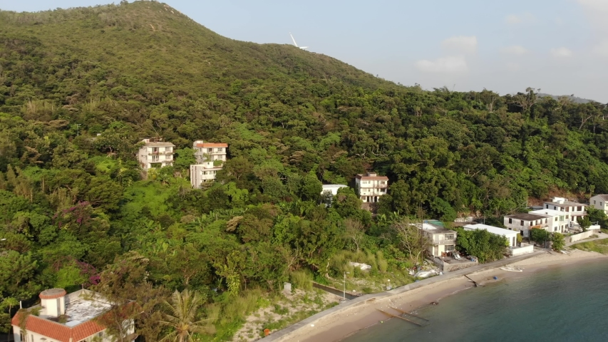 Aerial view the hilly coast of Lamma, a few villas among a lot of greenery. The view of the sea and the island of Hong Kong smoothly opens   Shutterstock HD Video #1040818934