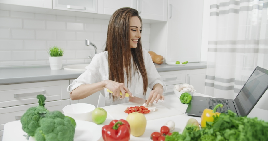 Attractive happy brunette chopping vegetables and having video chat sitting in kitchen with laptop, housewife communicating with friend | Shutterstock HD Video #1040894114