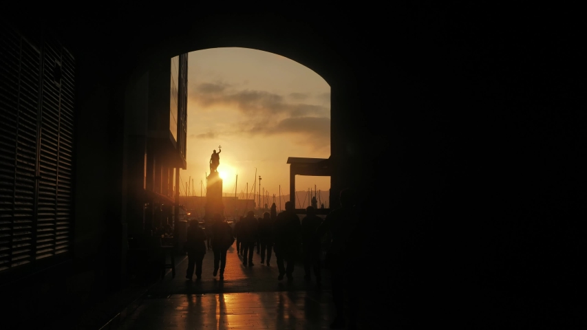 GIJON / Spain - 08 22 2018: GIJON, SPAIN - August 22, 2018: people walking at a plaza near the statue called Monumento a Pelayo, with the sunset creating beautiful silhouettes. | Shutterstock HD Video #1040909114