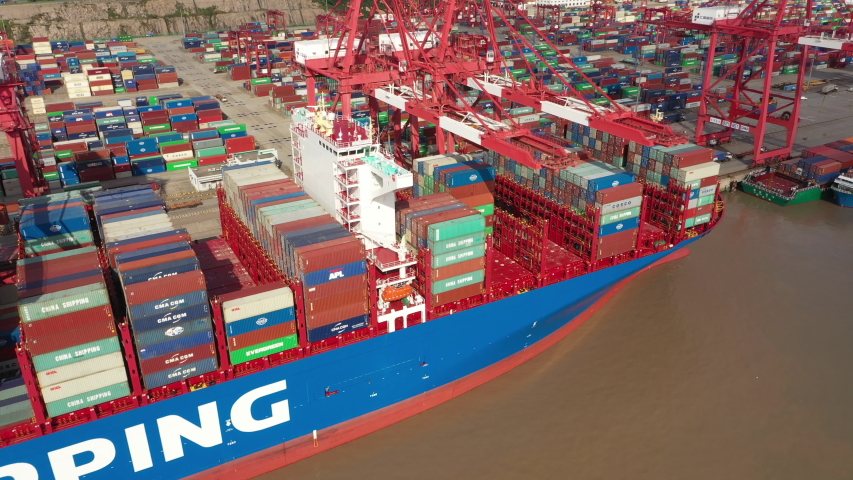 SHANGHAI, CHINA – SEPTEMBER 2019: Ascending drone shot of cranes and deck of cargo vessel in container terminal of deep-water Port of Shanghai in China   Shutterstock HD Video #1040923964