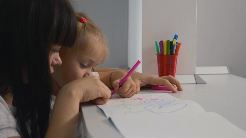 Happy family. Mom and daughter draw a picture in the album. Home schooling. Doing homework. Teamwork | Shutterstock HD Video #1041222064