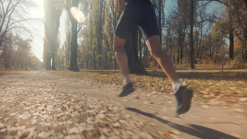 Running Man At Fall Park.Runner Man Fit Athlete Legs Jogging On Trail Ready To Triathlon.Triathlete Running,Sprinting And Endurance Workout Training.Marathon Runner Jog On Trail.Jogger Sport Concept | Shutterstock HD Video #1041348064