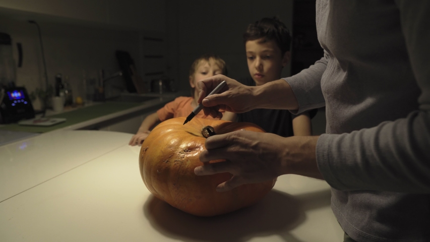 Happy halloween. Father and sons carving pumpkin on the table in the home. Family preparing for holiday. Top view. Close up. | Shutterstock HD Video #1041456604