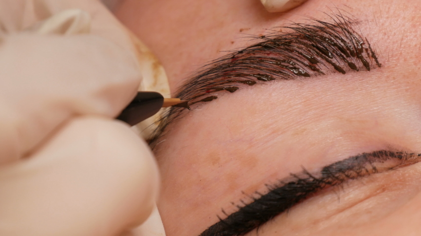 Microblading eyebrow tattoo, permanent makeup. A master in gloves, using special needle, injects pigment into the skin and stains the eyebrows using hair technique, making them natural, close-up view | Shutterstock HD Video #1041489724