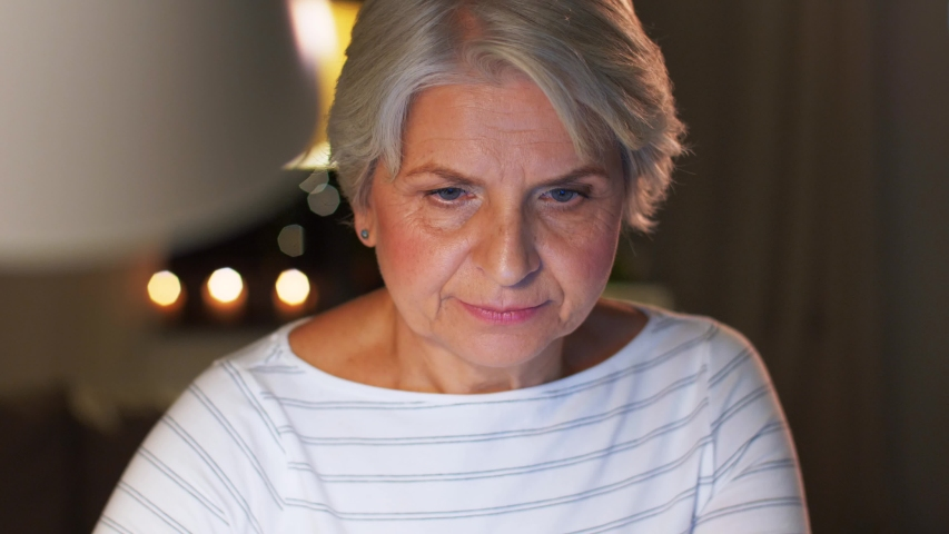 Technology, old age and people concept - senior woman with laptop at home in evening | Shutterstock HD Video #1041501544